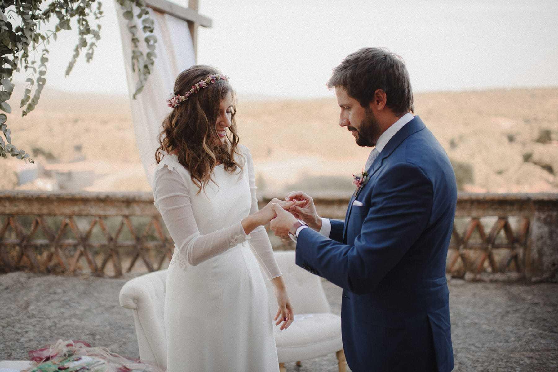 Novio poniendo el anillo de compromiso a la novia