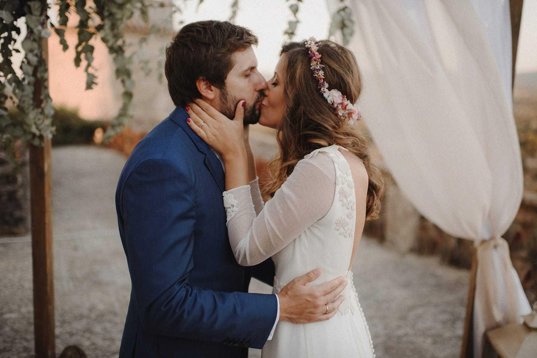 Novios besándose apasionadamente bajo un arco de flores