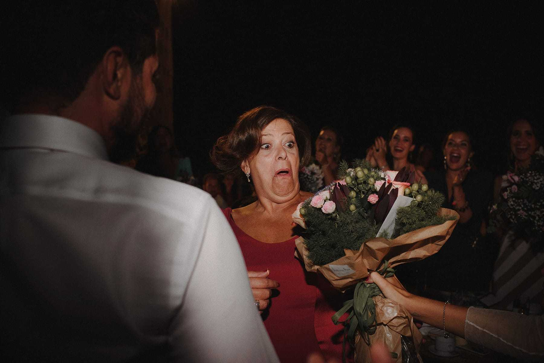 Madre de la novia sorprendida por el regalo de un ramo de flores de Flores en el columpio